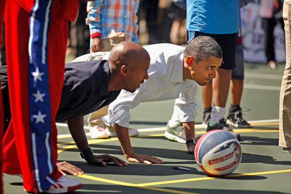 U.S. President Barack Obama (R) does pushups with retired NBA star Bruce Bowen during the annual Easter Egg Roll on the White House tennis court.