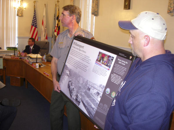 Curt Gaul, West District Ranger for the C&O Canal, and Charles Brown, right, hold up a sign about Williamsport which will be placed along the towpath at the Cushwa Basin. The sign was unveiled during a ceremony Monday night at town hall to celebrate the town's 225th birthday.