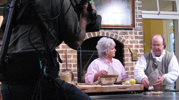 "Jim Gay during one of his final TV appearances several years ago, with Food Network's Paula Deen on ""Paula's Favorite Dishes,"" teaching her how to cook a meal in an open flame fireplace."
