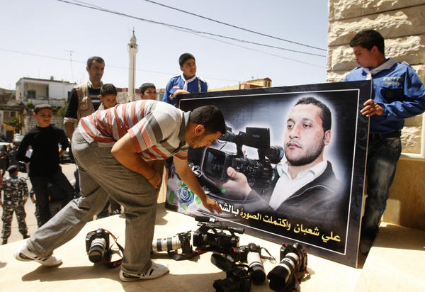 Colleagues lay down cameras in front of a portrait of Lebanese cameraman Ali Shaaban during his funeral in the southern village of Mayfadun on April 10, 2012. Lebanon's Al-Jadeed satellite television accused the Syrian army of shooting dead Shaaban, saying it opened fire at its team which was on Lebanon's side.