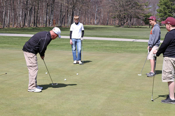 Ron Cox of Charlevoix, (from left) finishes putting on the sixth green Monday at the Charlevoix Golf Club, with Nick Wanczyk, 14, Hunter Cox, 14 and Jack Cox, 12. Ron Cox says he likes to golf with his grandsons any chance he gets.