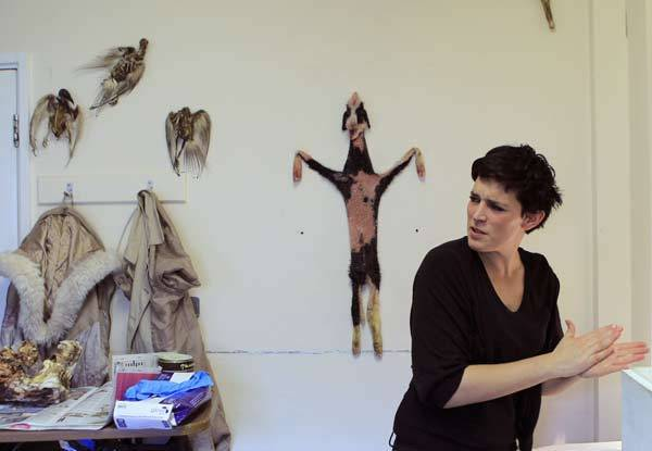 Artist and amateur taxidermist Charlie Tuesday Gates washes her hands after working on the lambskin pinned to the wall in London.