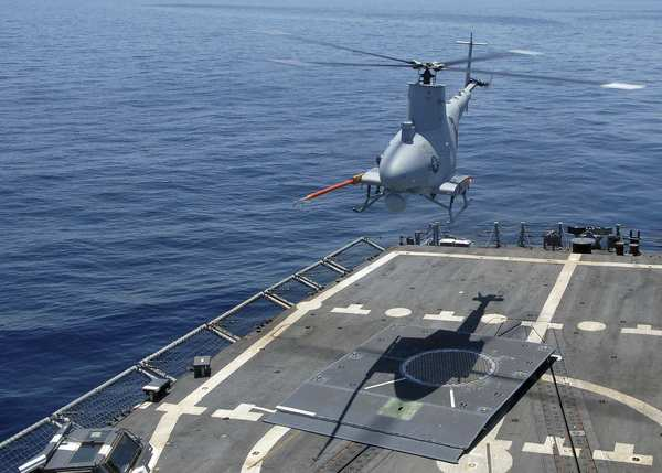 An MQ-8B Fire Scout, a helicopter drone developed by Northrop Grumman Corp., hovers over the flight deck of the guided-missile frigate McInerney in the Atlantic Ocean. The McInerney was preparing for a deployment to Latin America, where the Fire Scout was to be used against drug trafficking.
