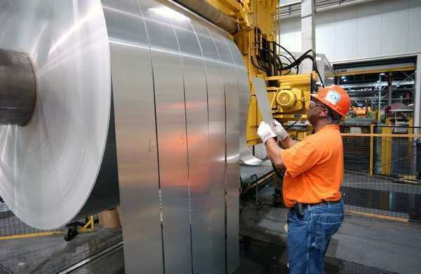 An Alcoa employee inspects finished rolls of aluminum as they come off the production line. Alcoa reported a first-quarter profit Tuesday.
