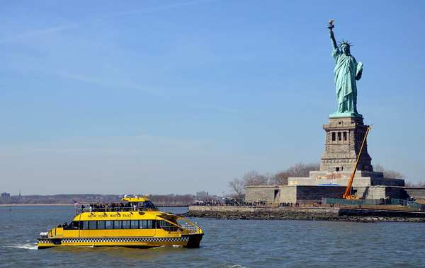 New York Water Taxi vessels cruise between the South Street Seaport and Pier 83 at West 42nd Street, passing the Statue of Liberty on the way.