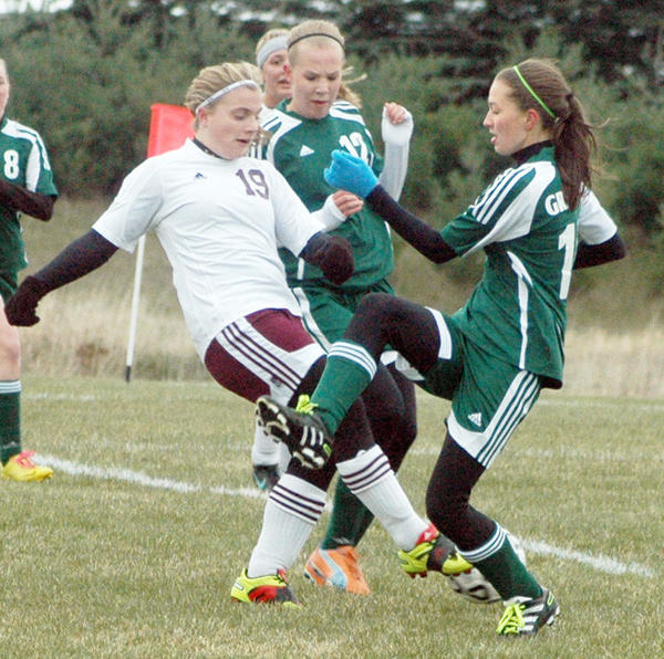 Charlevoix sophomore Katilin Hinkley (19) battles two Grayling players for possession of the ball Tuesday during a season-opening girls soccer match. The Rayders won, 4-2.