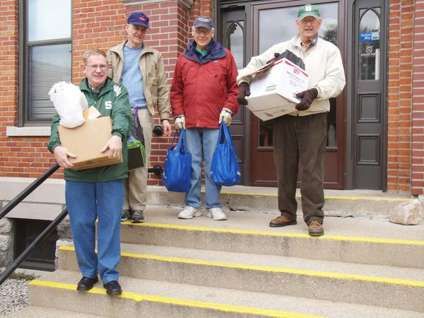 Brother Dan's Food Pantry volunteers (From left) Dick Clark, Jim Beer, Roy Pulaski and Jay Fennell help carry a supply of food to a pantry client's vehicle.