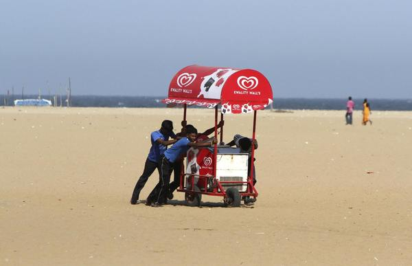 People move an ice-cream cart from the Marina beach after a tsunami alert was issued in the southern Indian city of Chennai April 11, 2012, following an earthquake which struck off Indonesia.