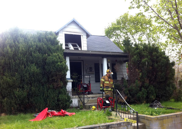 A firefighter emerges from 1044 Georgia Ave. in Hagerstown, where a house fire was reported Wednesday morning.
