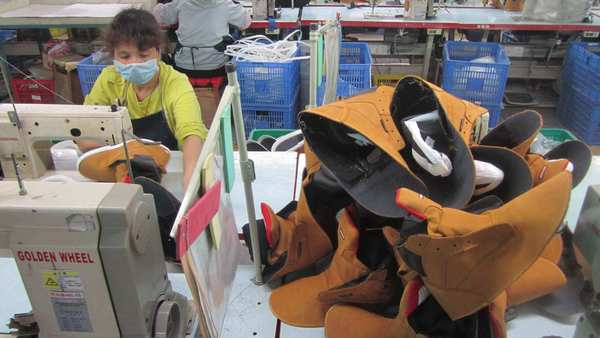 Workers make specialty footwear such as fire retardant boots and steel-toed shoes at Tony Zhang's factory in Huizhou, a city in southern China.