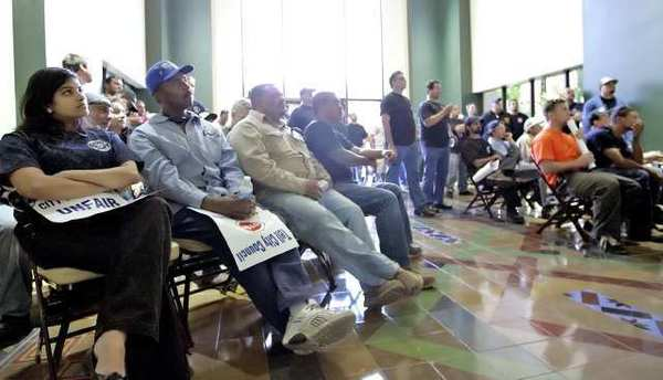 An overflow crowd of IBEW members and supporters fill the first floor of Glendale City Hall as they watch a TV screen displaying the city council meeting on Tuesday.
