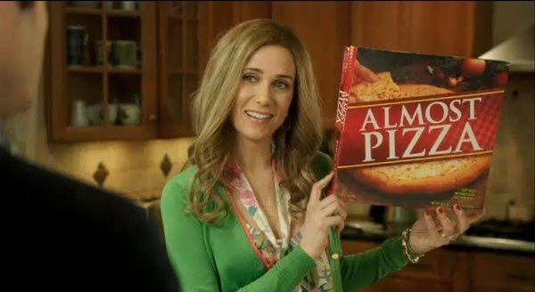 "Kristen Wiig stars in ""Almost Pizza,"" an SNL spoof of take-and-bake pizza commercials. Still, pizza sales are up."
