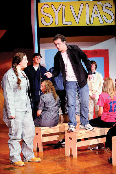 "Tessa Wiles, left, plays Natalie, a small-town girl captivated by a new guy in town, Chad, standing on the bench, played by Ryan Baker, in Clear Spring High School's production of ""All Shook Up."""