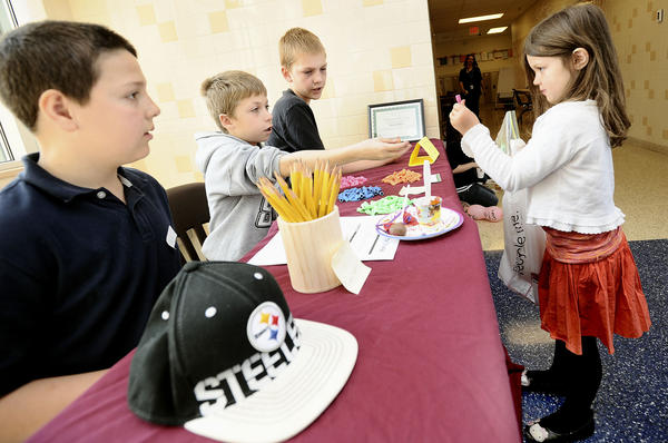 Erykah Damico shows Pencil Palace entrepreneurs, from left, Akif Yilmaz, Andrew Mack and Dawson Domer, what she wishes to purchase, an eraser, with her Tiger Tokens at the second annual economic fair Wednesday at Rockland Woods Elementary.