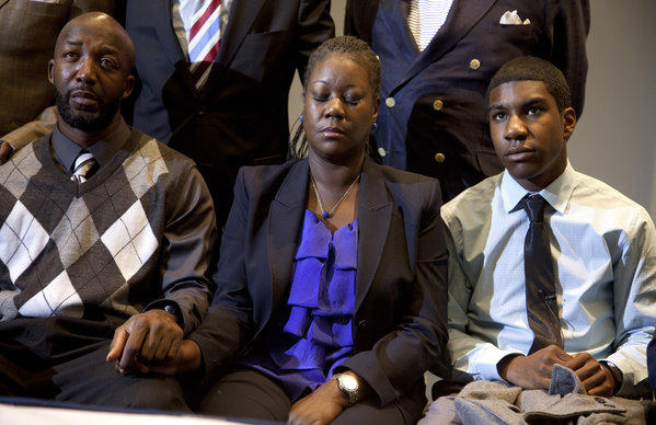 Trayvon Martin's parents, Tracy Martin, left, and Sybrina Fulton, and his brother Jahvaris Fulton watch a news conference where prosecutor Angela Corey announced a second-degree murder charge against George Zimmerman.