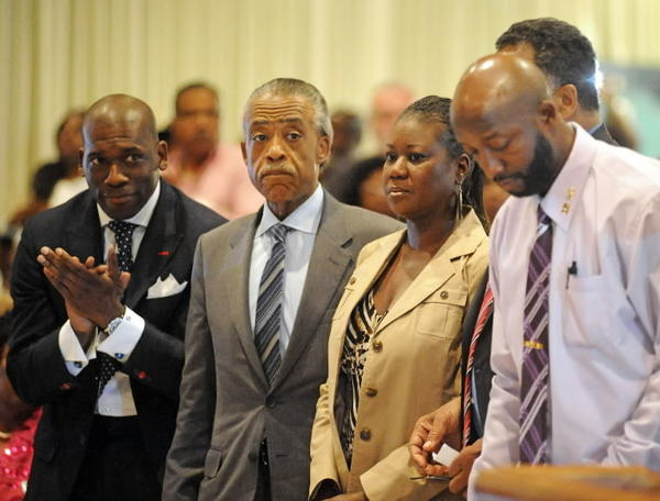 Tracy Martin and Sybrina Fulton, the parents of the late Trayvon Martin, stand with Rev. Al Sharpton and Pastor Jamal Bryant (left) during a Sanford City Commission meeting in Sanford, Florida, March 26.