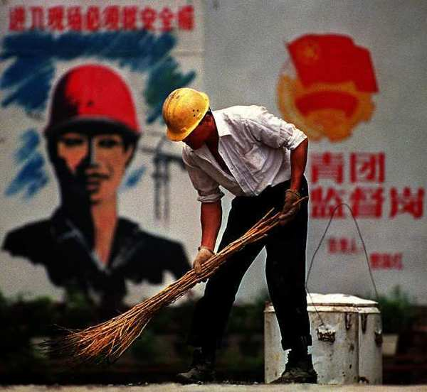 "A worker sweeps in downtown Beijing. The World Bank says that China's downturn is headed for a ""soft landing"""