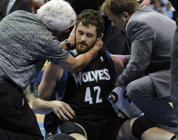 Minnesota Timberwolves forward Kevin Love is examined by a doctor after he took an elbow to the head.