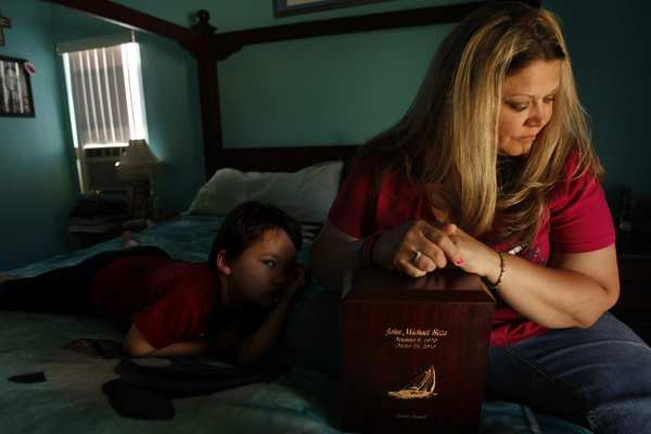 Megan Beza, with son Jacob, 5, leans on the wood box that holds her husband John's ashes. The box is carved with a picture of the sailboat they long talked about buying. John committed suicide in 2010.