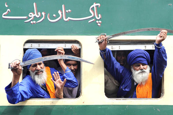 Indian Sikh Nihang (religious Sikh warriors) raise their swords after boarding a train to Pakistan on Wednesday. Thousands of Indian Sikh pilgrims are expected in Pakistan for the Baisakh celebrations, the Sikh New Year at the Sikh Shrine of Gurudwara Panja Sahib and Nankana Sahib, the birthplace of Sikh faith founder Guru Nanak Dev.