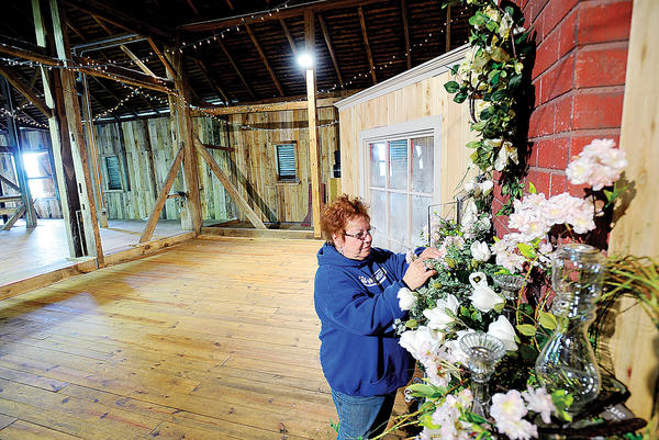 Joan Knode decorates the Barn at Springfield Farm in Williamsport for Saturday's Hitching Post Roundup Sale.