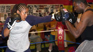 Laila Ali, daughter of US boxing legend Muhammad Ali, spars with John McClain during a workout at the Kronk Gym in Detroit.