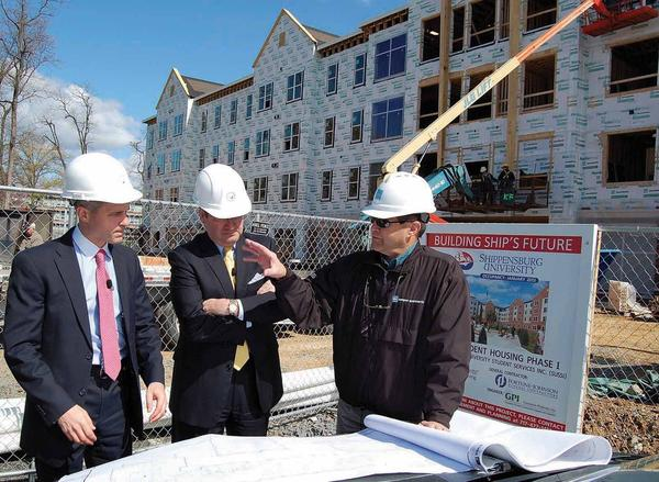 Construction project manager Mark Knepley, right, talks about new student housing being built at Shippensburg (Pa.) University. Knepley showed state Rep. Rob Kauffman, left, and University President William Ruud the project's progress.