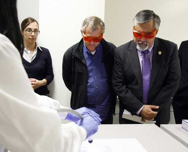 Burbank Mayor Jess Talamantes, right, wears orange glasses to see fluid evidence during a demonstration at the opening of the Verdugo Regional Crime Laboratory in the Glendale Police Department on Thursday. The lab is a tri-city partnership with Glendale, Burbank and Pasadena, and the ATF also partnered.