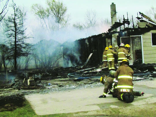 Firefighters work to extinguish a fire that destroyed the home of Harley and Eva Gage in Westport on Thursday. American News Photos by Scott Feldman