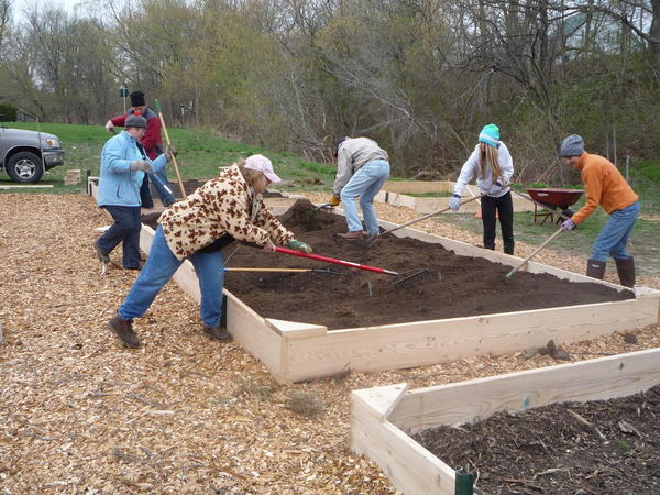 Volunteers and gardeners work to create raised garden beds for the Petoskey Community Victory Garden.