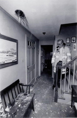 Wethersfield Firefighter John S. McAuliffe examines the damage at Wanda and Robert Donahue's home at 461 Church St. caused by a falling meteorite in 1982.
