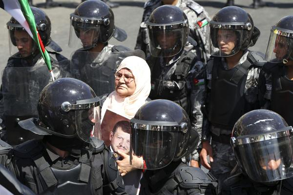 A pro-government supporter holds a picture of Jordan's King Abdullah as she stands amongst riot police in Amman April 13, 2012. Anti-government protesters also organized a protest following Friday prayers.