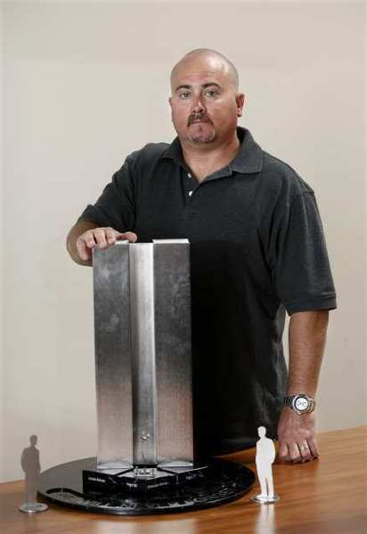 Long Beach artist Patrick Vogel poses with a model of his winning design for the city of Huntington Beach's 9/11 memorial design contest Tuesday.
