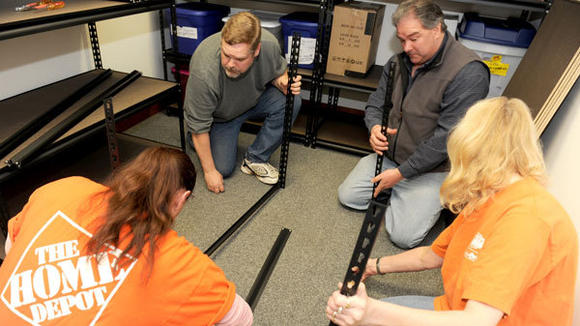 Assembling a storage shelf for the first office the Children's Bereavement Network has occupied are Team Depot members Michelle Madden, Paul Bertges, Allen Courtney and Pearl Stahlbuck (l-r):