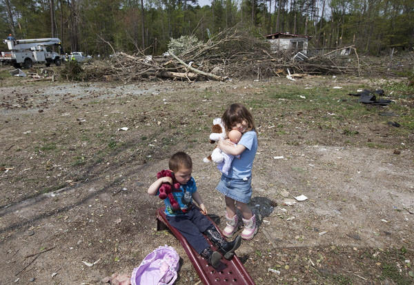 David Lewis, 2, and his sister, Ciara Lewis, 4, play with dolls from American Red Cross disaster services in front of their house, which was damaged by Tornado, in Hayes area, Gloucester on Monday. Nobody was injured at their family but their next door neighbor was killed by Tornado.