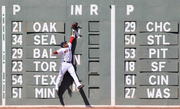 Red Sox left fielder Darnell McDonald makes a leaping first-inning catch in Boston's home opener vs. the Rays on Friday.