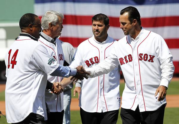 Former Red Sox players, from left, Jim Rice, Dwight Evans, Jason Varitek and Tim Wakefield meet on the field at Fenway Park Friday prior to throwing out the first pitch.