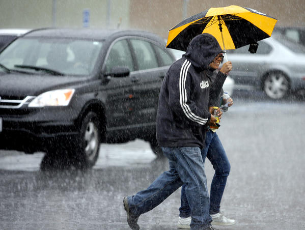 Fernando and Marci Gomez make their way across the Whole Foods Parking lot on the 300 block of N. Glendale Ave. in Glendale during a stormy Friday the 13th, April 13, 2012.