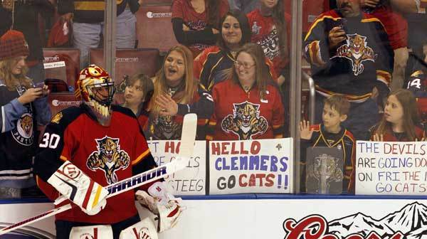 Fans look from behind the glass at Florida Panthers' goalie Scott Clemmensen as the team skates on the ice before they play the New Jersey Devils in the first game of the NHL Playoffs at the BankAtalntic Center in Sunrise, Florida, Aril 13, 2012.
