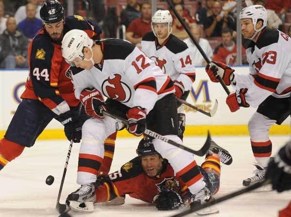 Ed Jovanovski of the Panthers gets knocked to the ice as Alexei Ponikarovsky of the Devils battle for the puck in the first period.New Jersey Devils vs. Florida Panthers Round 1 NHL Playoffs.