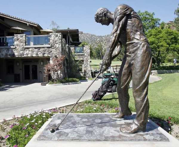 A statue of a golfer with the club house and pro shop behind it at DeBell Golf Club in Burbank. An oversight committee for the club implemented cost-cutting measures this week.