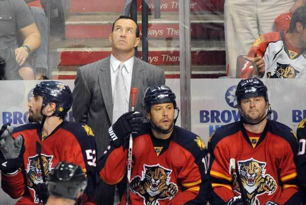 Panthers head coach Kevin Dineen checks the scoreboard in the second period. New Jersey Devils vs. Florida Panthers Round 1 NHL Playoffs.