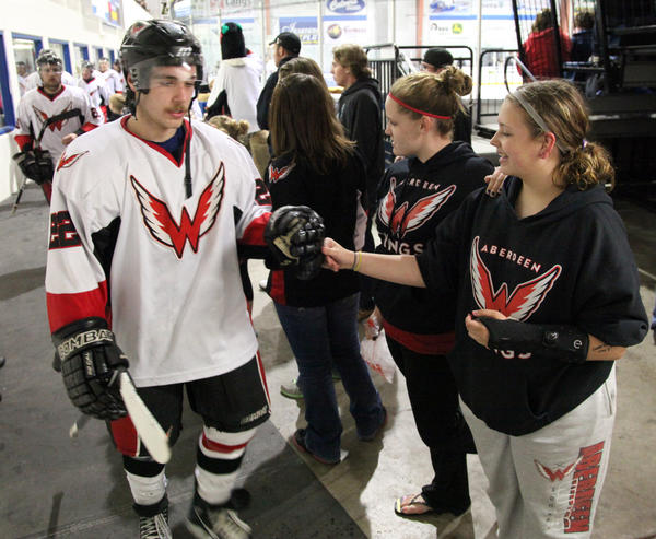 Paul Prescott, left, is greeted by Amber Engram, 13, right, and Cierra Hubbs, 14, as Prescott and his teammates head for the locker room at the end of the second period of Friday night's NAHL playoff game against the Bismarck Bobcats at the Odde Ice Center. American News Photo by John Davis