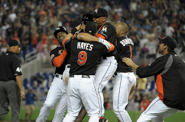 Miami Marlins first baseman Gaby Sanchez in surrounded by teammates after his RBI double scored teammate Chris Coghlan.
