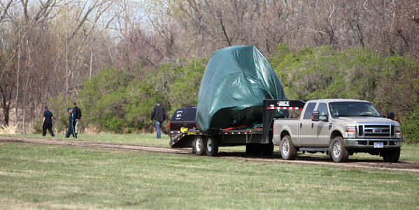 A tarp covers the CareFlight helicopter as it was hauled away from the crash site this morning.