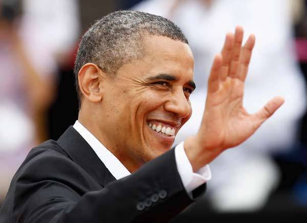 President Barack Obama waves as he arrives at the convention center, where the Americas Summit is being held, in Cartagena, Colombia.
