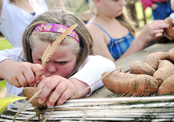 Skylar Wilson, 5, of Boonsboro learns to makes a German scarecrow like ones made in the 1800's using feathers and sweet potatoes, Saturday during the Rural Heritage Museum spring open house at the Washington County Agricultural Education Center in Hagerstown.
