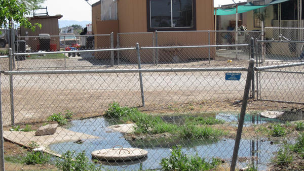 A mobile home is visible not far from a standing pool of overflowing septic tank water at a mobile home park located at 997 Evan Hewes Highway in El Centro.