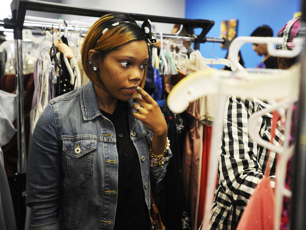 Karisma Dorsey, 17, a student at Western High School and Baltimore City resident, sorted through dresses at Julie Box Hair Salon, which gave away 80 gowns to underprivileged young women from the area for the Prom Gown Bazaar and Giveaway.