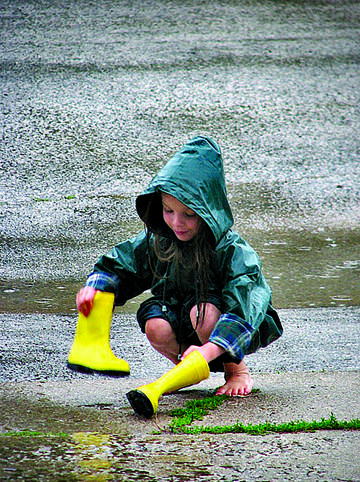 "Kendall Jacobson, 7, plays in the rain, while she and her mother were out walking their dog on Sunday. Kendall said she wasn't bothered by the rain and wind. ""I didn't want to stay inside,"" she said. American News Photo by Kevin Bennett"